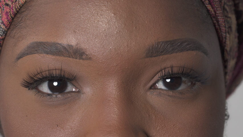 Brown female eyes looking at camera. Close-up portrait shot of a beautiful African American woman   Shutterstock HD Video #1047264700