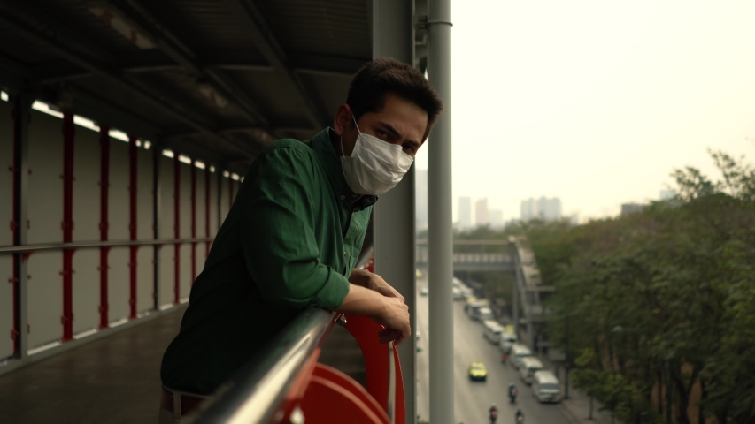 A man wearing mask protective for spreading of disease virus Covid-19 and air smog pollution with PM 2.5 standing on skywalk at chatuchak district in  Bangkok city, Thailand. | Shutterstock HD Video #1047323320
