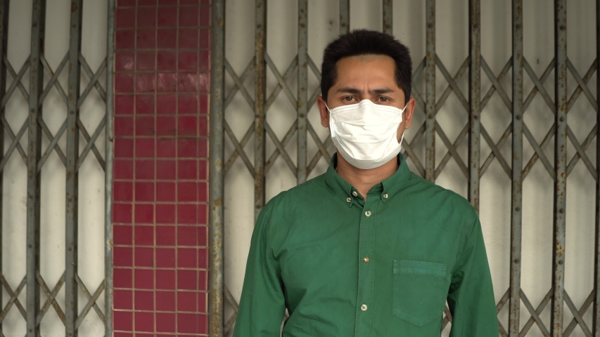 A man wearing mask protective for spreading of disease virus Covid-19 and air smog pollution with PM 2.5  on old gate steel. | Shutterstock HD Video #1047324880