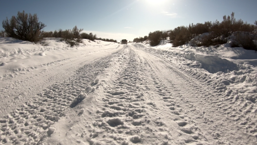 Driving on snow covered road winding through the desert following truck ahead as it makes way down the path. | Shutterstock HD Video #1047408490