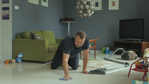 Man cleaning at modern looking home, scrubbing the floor