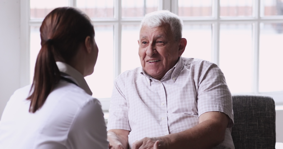 Senior elder man patient talking to caring female doctor physician caregiver at nursing home in hospital holding hands explaining well-being get support and medicare services at medical checkup visit. | Shutterstock HD Video #1047837520