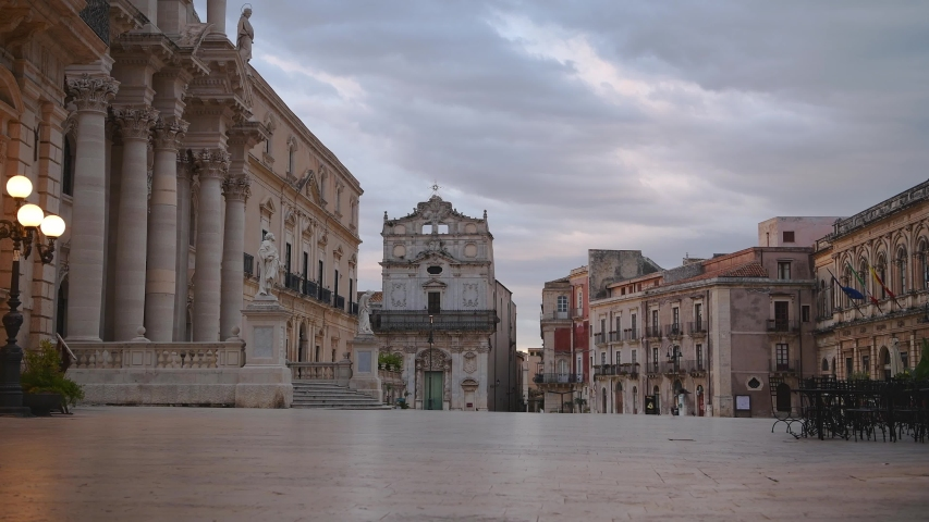 Pigeons fly over the empty main square Piazza Duomo in Ortygia island at sunrise in province of Siracusa in Sicily  | Shutterstock HD Video #1047980380