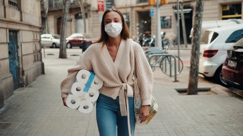 Woman walking in medical mask with toilet paper and packs of pasta food shopping bags during the quarantine coronavirus COVID-19 pandemic in 2019-2020 | Shutterstock HD Video #1048422220