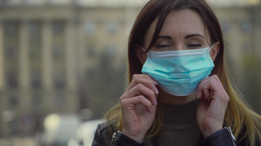 Woman putting on surgical mask for corona virus prevention standing at city square . Dangerous COVID-19 infection | Shutterstock HD Video #1049575120