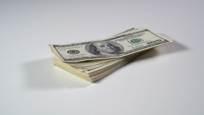 A bundle of dollar bills falls on a white table. Close-up | Shutterstock HD Video #1049640820