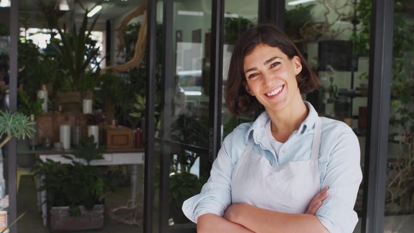 Female owner of florists shop standing in doorway of store looking into camera and smiling - shot in slow motion | Shutterstock HD Video #1049651590