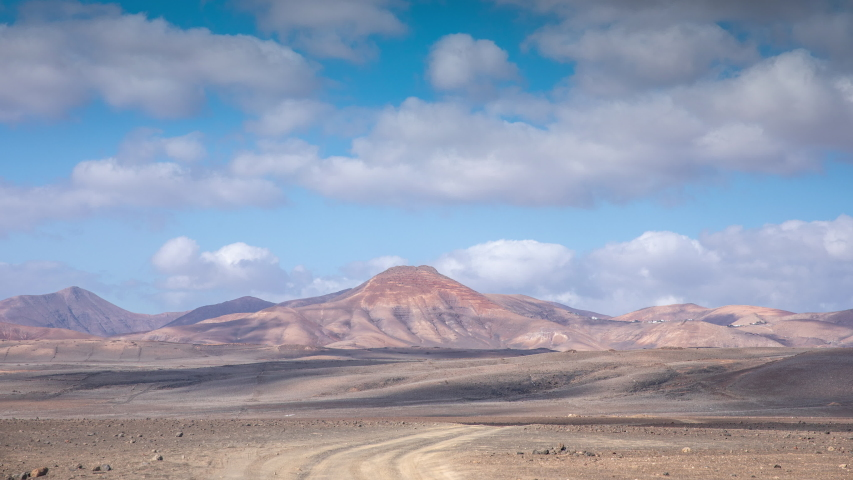 Timelapse of clouds passing over wild arid landscape of the Timanfaya National Park in Lanzarote. | Shutterstock HD Video #1049653420