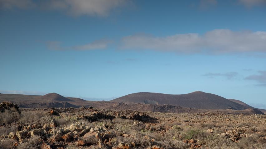 Panning timelapse of clouds passing over wild arid landscape of Volcano de Bayuyo in Fuerteventura. | Shutterstock HD Video #1049661310