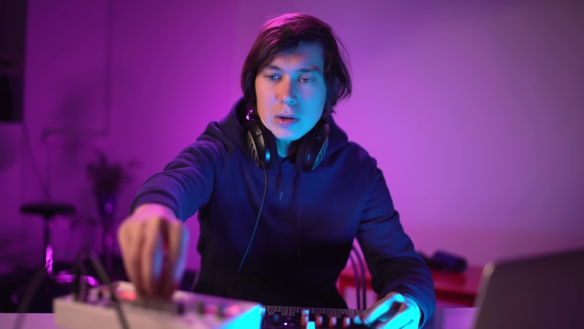 Portrait handsome man DJ playing music at home recording studio workshop. Student learns to write creative atmosphere music. Online education training. Sound beat maker. Colorful Neon light | Shutterstock HD Video #1049707990