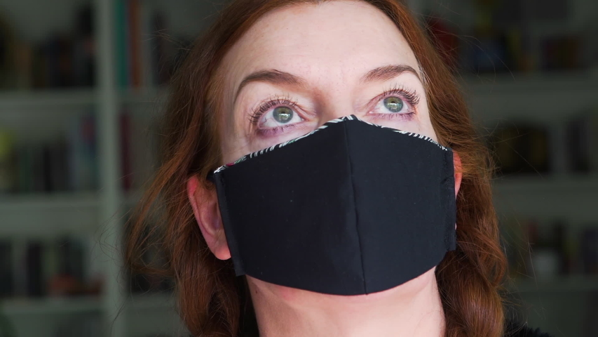 Portrait of an an experienced fashion designer wearing the face mask that she created at home  from recycled fabric as a protection against viruses, disease and germs | Shutterstock HD Video #1049712430