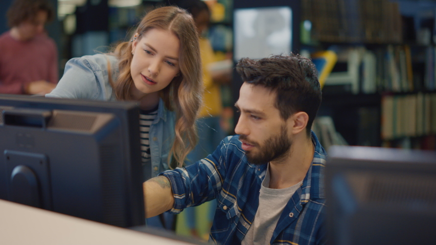 University Library: Focused Bright Caucasian Girl and Talented Hispanic Boy Study for Exams, Work on Assignment, Use Computer, Point at the Screen, Talk, Look for Solution, Explain Subject | Shutterstock HD Video #1049866990