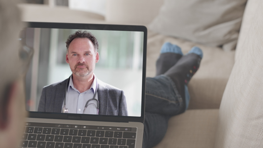 Online video call via laptop of male doctor consulting sick man lying on sofa listening. Medicine, healthcare, Technology | Shutterstock HD Video #1049943040