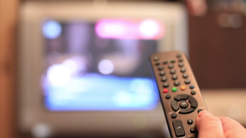 A man's hand switching channels on his TV with the remote control | Shutterstock HD Video #1050400