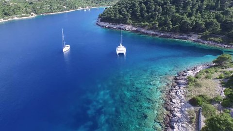 Aerial, panormaic, scene traveling from a rocky coast to a catamaran anchored in a bay of the Dalmatian Coast, Croacia. Idyllic island with transparent water and copious vegetation.