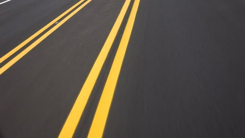 Driving on newly paved road, double yellow lines converge, close up, driver POV. 4K UHD 3840x2160
