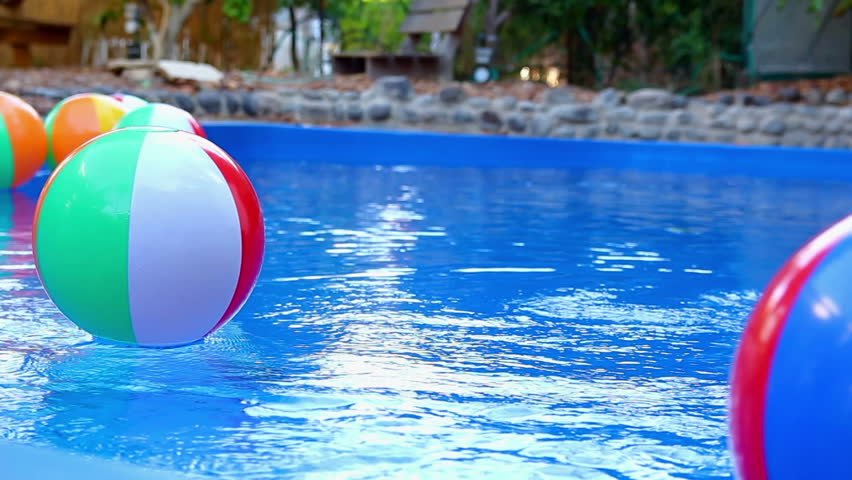 Beach Ball In Water colorful beach ball thrown into the water in the pool stock