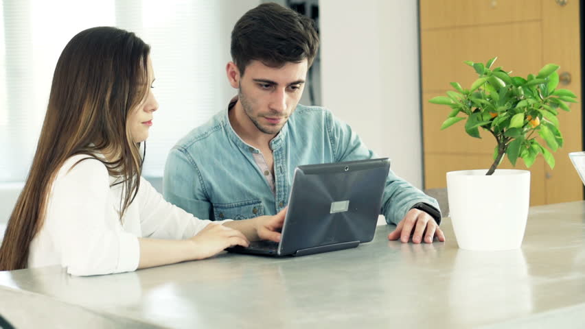 Group of friends talking over laptop by table at home     Shutterstock HD Video #10557977