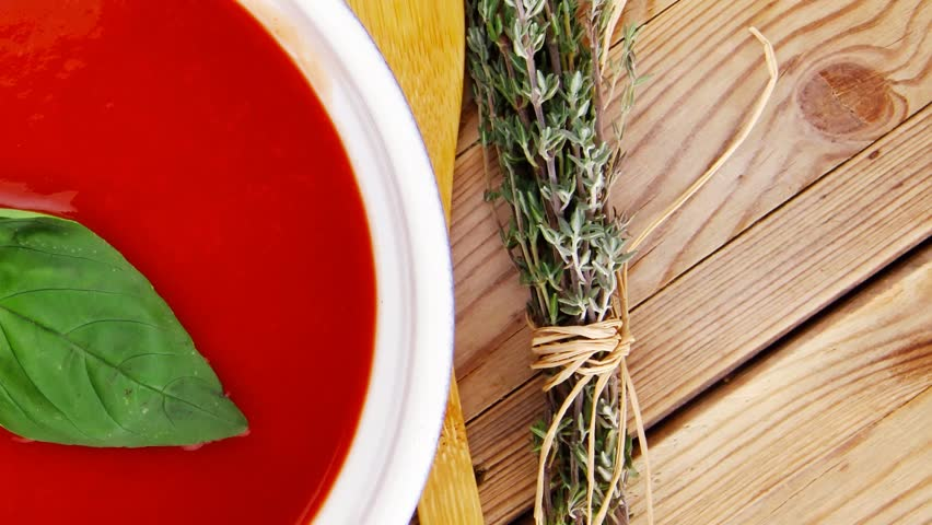 Hot fresh diet tomato soup with basil thyme and dry pepper in big bowl on wood table 1920x1080 intro motion slow hidef hd | Shutterstock HD Video #10563800