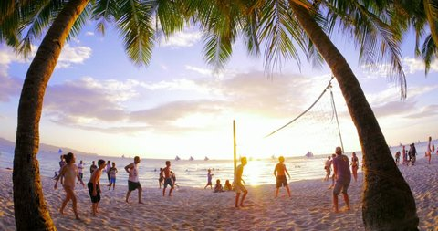 BORACAY, PHILIPPINES 9 FEB 2015: Unidentified tourist play beach volley ball at sunset on sandy beach of tropical island while being on summer holidays