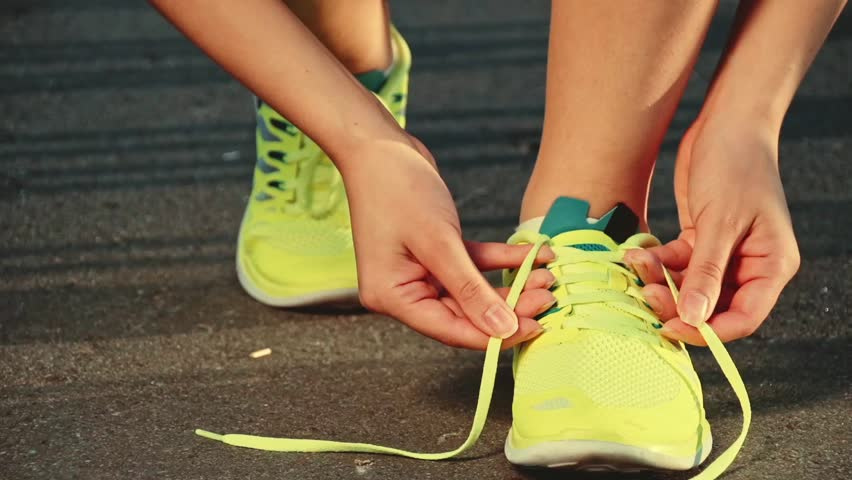 Slow motion: running shoes. Barefoot running shoes closeup. Female athlete tying laces for jogging on road in minimalistic barefoot running shoes. Runner getting ready for training. Sport lifestyle.