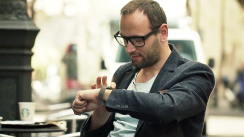 Handsome man with smartwatch sitting in cafe in city