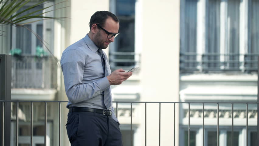 Young businessman using smartphone standing on balcony   | Shutterstock HD Video #10647968