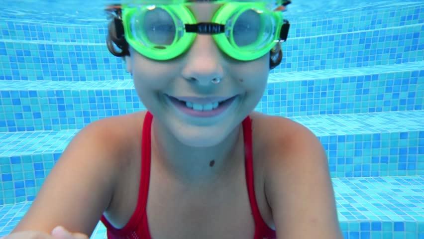 Happy girl in goggles swim underwater in pool. Close up