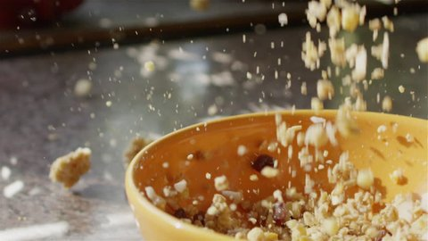 SLOW MOTION CLOSE UP: Whole grain cereal falling into bowl