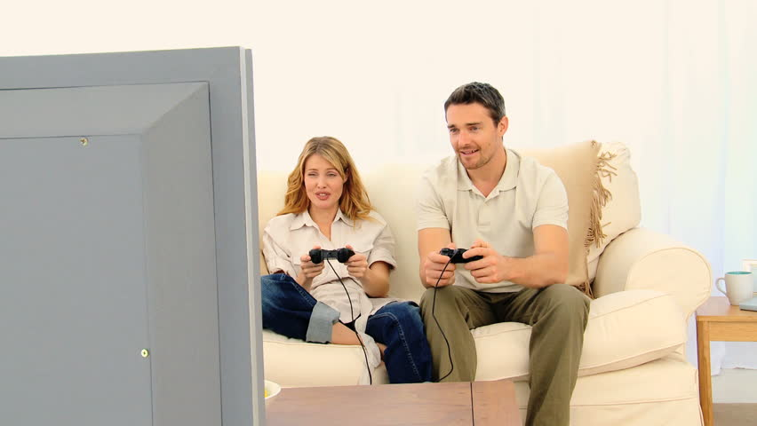 Pretty couple playing a video game on their sofa