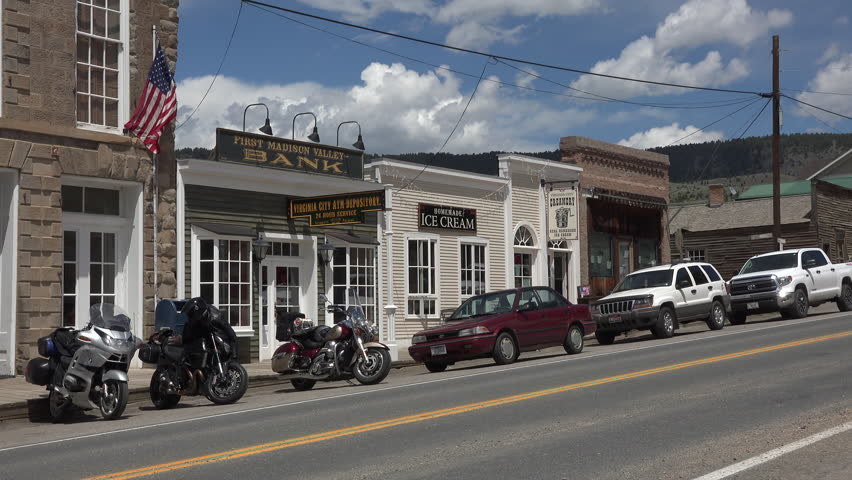 ENNIS, MONTANA - JUN 2015: Ennis Montana historic main street motorcycles traffic 4K. The rural culture extends to it's main street with craft, museum, tourist shops, saloons and stores.