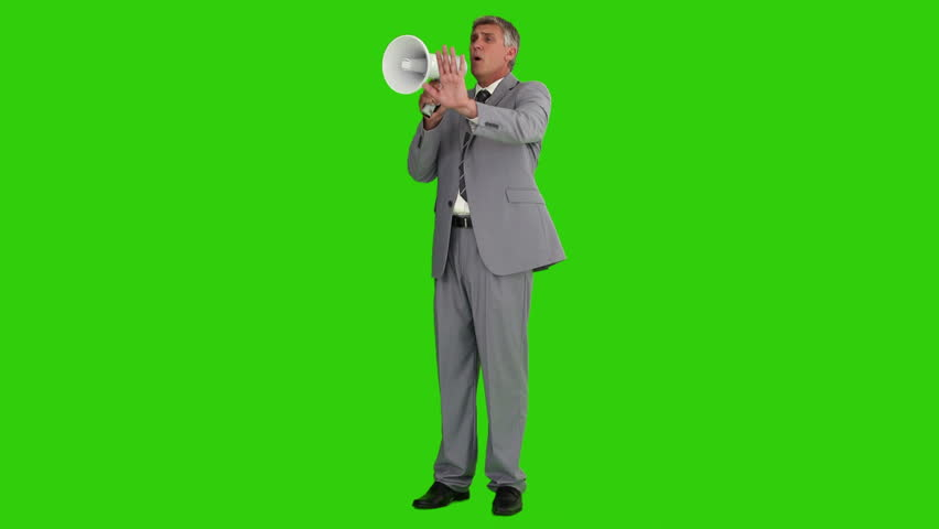 Elderly businessman giving orders through a megaphone against a green screen