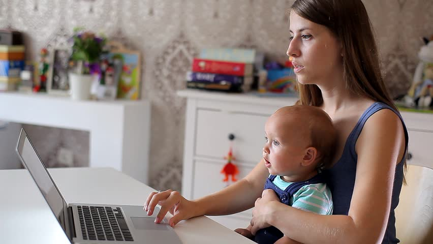 Young Mother with a Child Working at a Computer