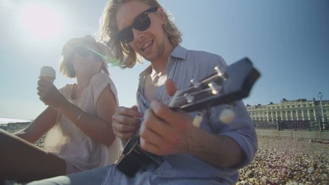 4K Cool couple on a beach having fun with a ukulele and ice cream in slow motion, shot on RED EPIC