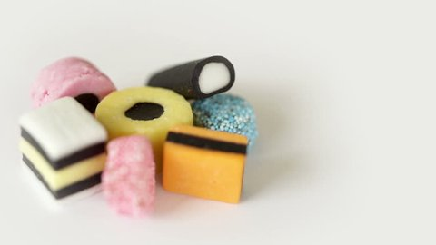 Camera move round a heap of liquorice sweets. Camera slowly orbits around a pile of various liquorice sweets then stops.