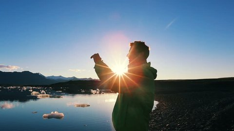 Silhouette of Young Male Tourist Taking Pictures with Smart Phone at Sunrise on Adventure Vacation.