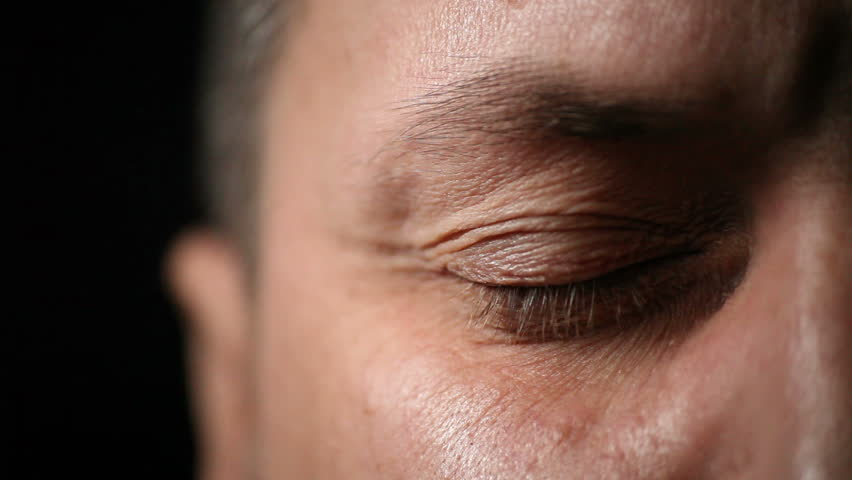 Closeup of adult man eye against dark background