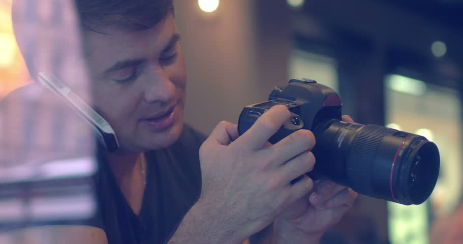 Male photographer is sitting in cafe, watching photos in the camera and talking on the phone holding it with shoulder. Shot is made through cafe show window. | Shutterstock HD Video #10818680