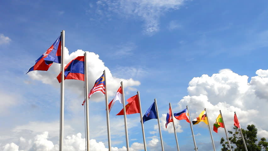 AEC or ASEAN flag waving atop among Southeast Asia nation flags on blue sky backgrund