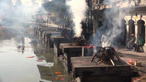 KATHMANDU, NEPAL - 5 JANUARY 2015: Workers burn the remains of recently passed away people at the cremation ghats in the Pashupatinath temple complex in Kathmandu.