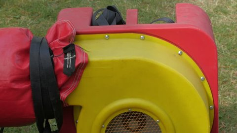 A red blower used to inflate the zorb ball. This is used to other inflatable objects as well