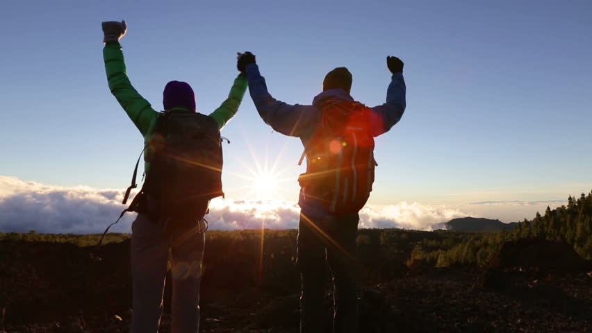 Success, achievement and accomplishment concept with hiking people cheering and celebrating of joy with arms raised outstretched up on trekking hike outside. Hikers having fun at sunset. | Shutterstock HD Video #10884611