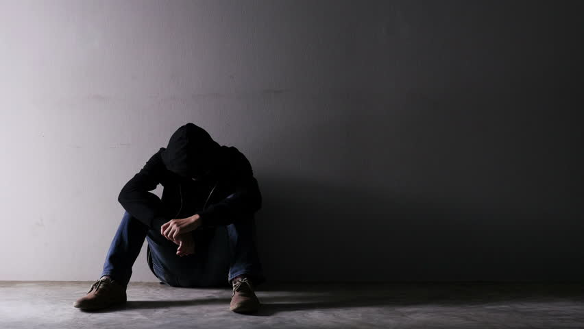 Asian troubled man wearing a hood in an empty room