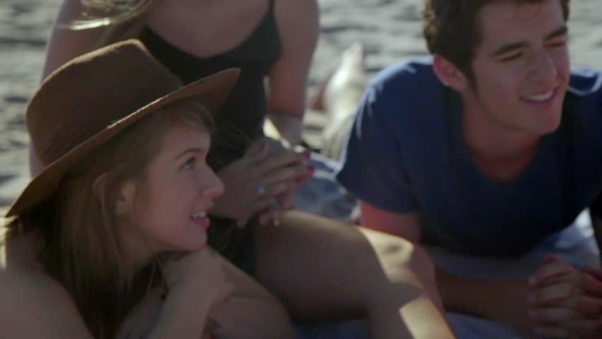 Medium shot of attractive teenagers on the beach