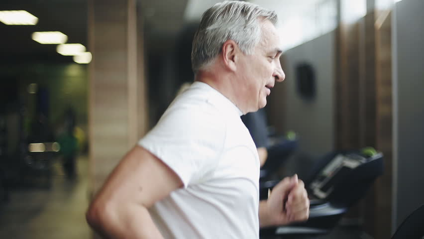 Senior man exercising on a treadmill in the gym. Right profile face footage