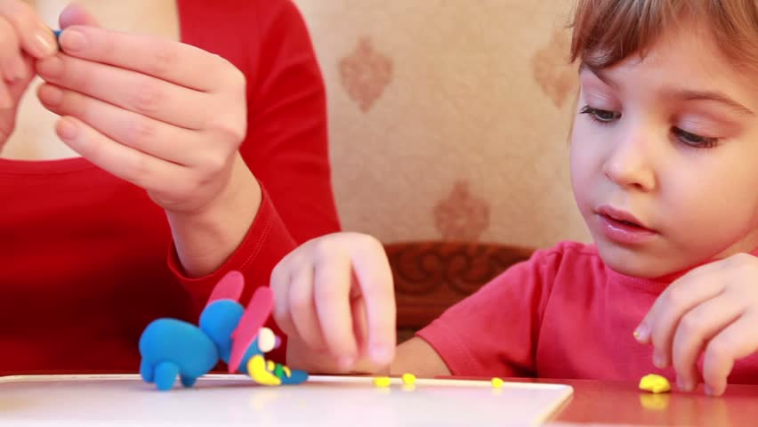 girl sculpts plasticine on table, watch with interest