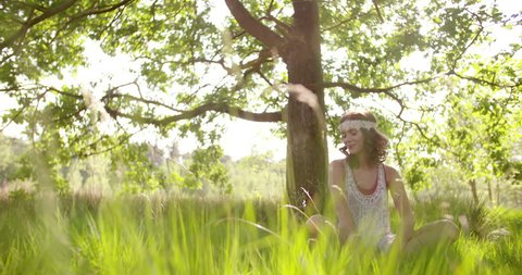 Laughing girl in boho fashion sitting happily in lush green grass in a summer park under sunlit trees, Panning in Slow Motion