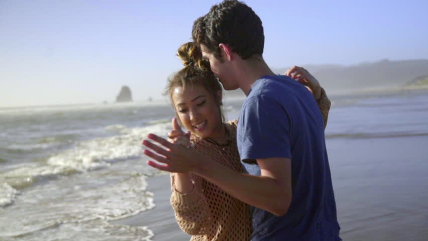 Teenage couple dancing together at the beach