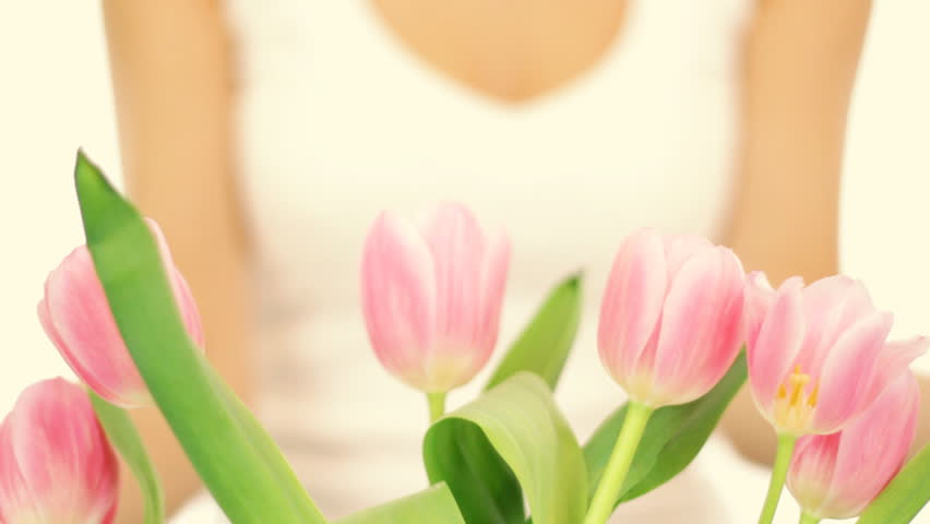 Young romantic woman smell spring tulips, isolated