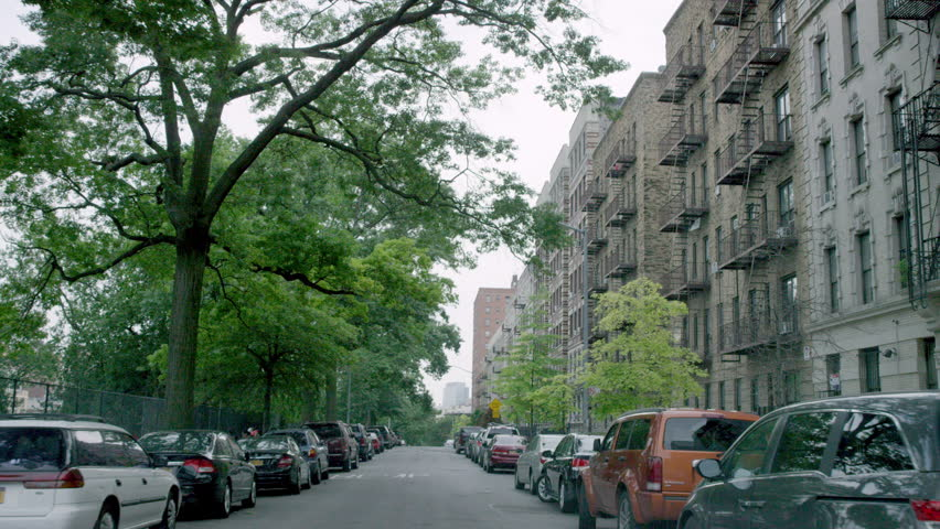 NEW YORK - JULY 12, 2015: driving down tree-lined street viewed through windshield in the Bronx, NY. The Bronx is the northernmost borough in NYC.